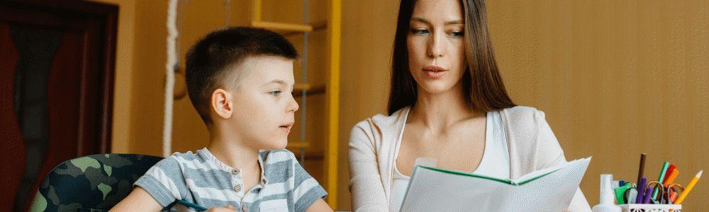 Jak sobie poradzić z rozpieszczonym dzieckiem? - chłopiec odrabia lekcje z pomocą mamy