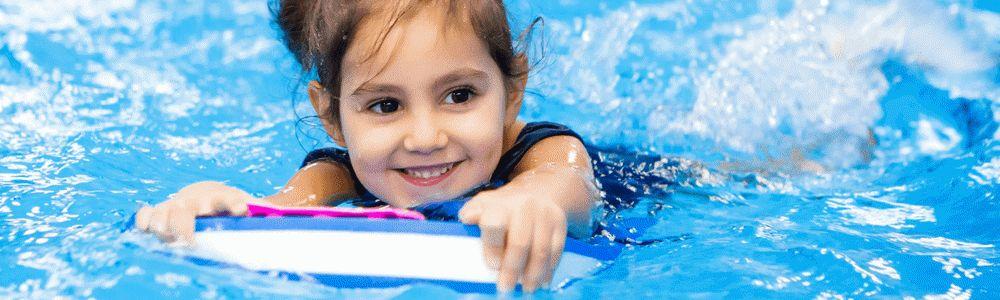 Zainteresowania małego dziecka - uśmiechnięta dziewczynka w wieku przedszkolnym pływa w basenie z pomocą deski