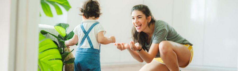 Jak dziecko zaczyna chodzić - maluch samodzielnie idzie w stronę uśmiechniętej mamy