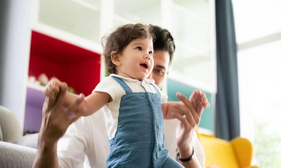 Kiedy dziecko zaczyna chodzić - małe dziecko stawiające pierwsze kroki z pomocą taty