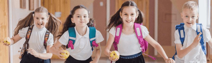 Uśmiechnięte dzieci z plecakami na plecach biegną szkolnym korytarzem