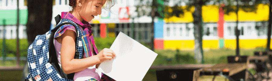 Jak wybrać plecak dla pierwszoklasisty - uśmiechnięta dziewczynka z kolorowym plecakiem na tle szkoły