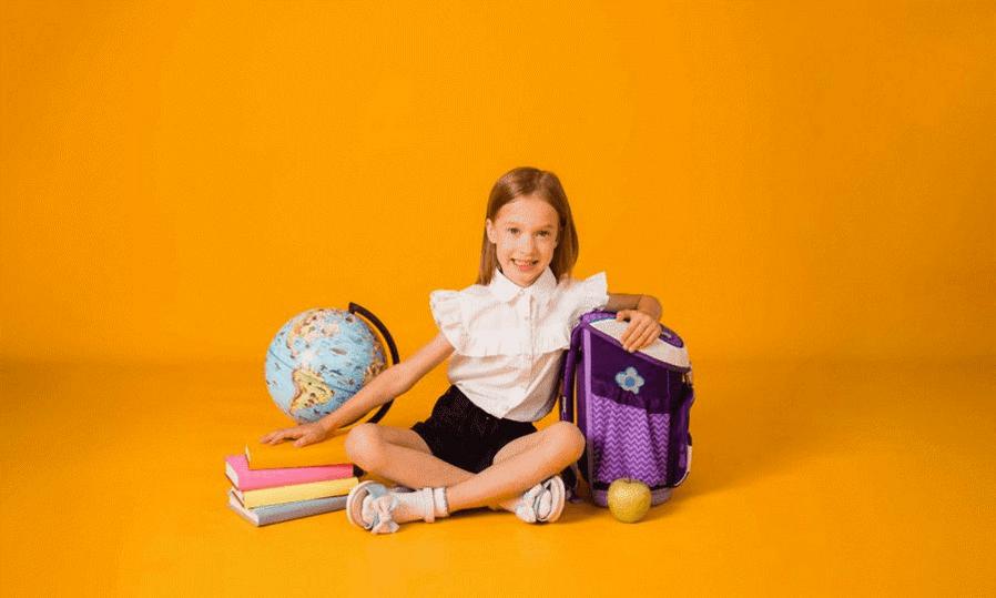 Plecak dla pierwszoklasisty - jaki wybrać? Uśmiechnięta dziewczynka z plecakiem i wyprawką szkolną siedząca na podłodze